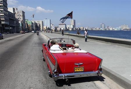 Tourists ride a U.S.-made 1957 Chevrolet Bel-Air convertible car on Havana's seafront boulevard 'El Malecon' May 21, 2013. REUTERS/Desmond Boylan