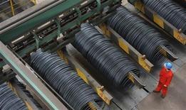 Un empleado junto a unas bovinas de acero en una fábrica en Dalian, China, oct 18 2013. La economía de China creció entre julio y septiembre a su ritmo más rápido este año, impulsada por la inversión, aunque los analistas se preguntan si el vigor continuará en los próximos meses. REUTERS/China Daily