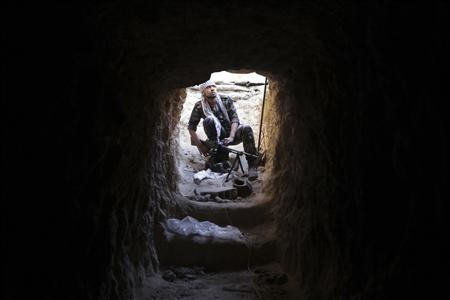 A Free Syrian Army fighter carries his weapon as he takes position inside a tunnel in Deir al-Zor October 15, 2013. Picture taken October 15, 2013. REUTERS/Khalil Ashawi