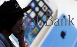 A pedestrian using a mobile phone walks past a shop window of Japan's mobile phone operator Softbank in Tokyo, September 20, 2013. REUTERS/Yuya Shino