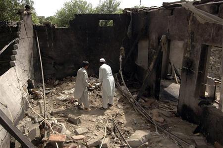 Residents stand inside a damaged house after a missile attack in Damadola village of the Bajaur tribal region in Pakistan May 15, 2008. REUTERS/Ammad Waheed