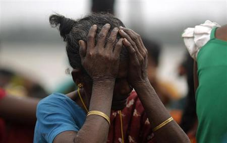 A woman holds her head after Cyclone Phailin hit Sunapur village in Ganjam district in Odisha October 13, 2013. REUTERS/Adnan Abidi