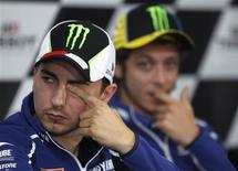 Yamaha MotoGP rider Jorge Lorenzo of Spain (L) rubs his eye as his teammate Valentino Rossi of Italy watches during the post-qualifying news conference ahead of the Australian Motorcycle Grand Prix, at Phillip Island Circuit October 19, 2013. REUTERS/Brandon Malone