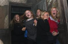 "A group of girls react to a live actor character at the ""13th Floor"" haunted house in Denver October 18, 2013. REUTERS/Rick Wilking"