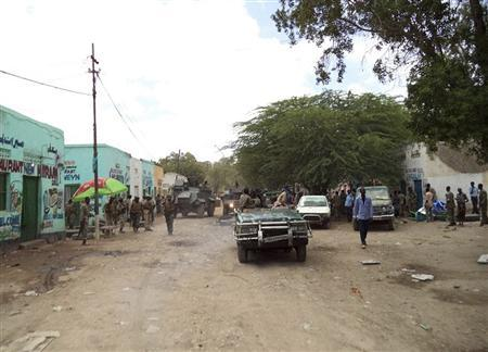 Somali government soldiers gather at the scene of a suicide bomb attack within a military base tea shop in Somalia's town of Baladweyne October 19, 2013. REUTERS/Stringer