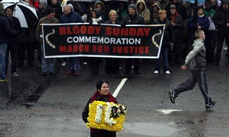 Linda Nash whose brother William Nash was one of 14 killed carries a floral tribute at a memorial service to mark the 40th anniversary of Bloody Sunday in Londonderry January 29, 2012. REUTERS/Cathal McNaughton