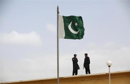 A Pakistani flag flies on a mast as paramilitary Frontier Corps soldiers talk while guarding at Karachi's District Malir prison, August 23, 2013. REUTERS/Akhtar Soomro/Files