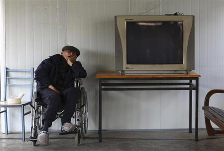 A man sleeps on a wheelchair next to a television set at a nursing home on the Double Ninth Festival, or Chongyang Festival, in Kunming, Yunnan province October 13, 2013. REUTERS/Wong Campion