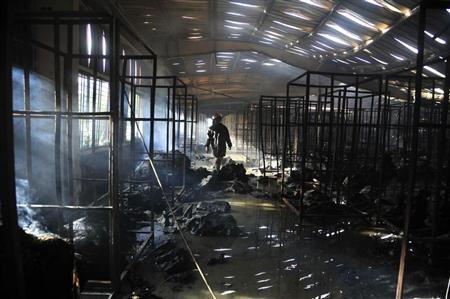 A firefighter inspects a burnt garment factory after a fire in the Bangladeshi town of Gazipur, 40 km (25 miles) north of Dhaka October 9, 2013. REUTERS/Khurshed Rinku