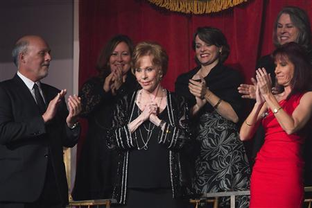 Comedian and actress Carol Burnett (C) is applauded by her husband Brian Miller (L) and members of her private box as she arrives to be feted during the presentation of the 2013 Mark Twain Prize for American Humor at the Kennedy Center in Washington, October 20, 2013. REUTERS/Jonathan Ernst