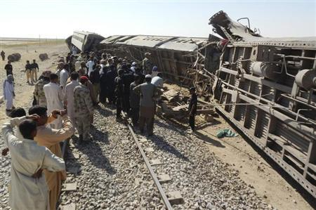 Officials, rescue workers and residents gather near the passenger train derailed after it was hit by a bomb attack in Dera Murad Jamali, located in the Nasirabad District of Balochistan province, October 21, 2013. REUTERS/Amir Hussain
