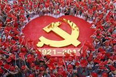 Дети с флагами у герба КНР в начальной школе в Цзаочжуане 29 июня 2011 года. Руководство Китая призвало чиновников прикладывать больше усилий для возрождения экономики, поскольку восстановление пока не стабильно. REUTERS/China Daily