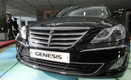 An employee of Hyundai Motor walks past the company's luxury sedan 'Genesis' displayed for visitors after its annual general meeting of stockholders at the automaker's headquarters in Seoul March 11, 2011. REUTERS/Jo Yong-Hak