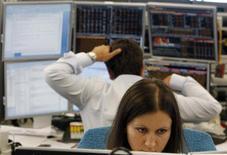 Трейдеры в торговом зале инвестбанка Ренессанс Капитал в Москве 9 августа 2011 года. Российские фондовые индексы в ходе торгов понедельника практически не отошли от достигнутых на прошлой неделе максимумов восьми месяцев, но спрос перекочевал в бумаги Россетей и Уралкалия. REUTERS/Denis Sinyakov