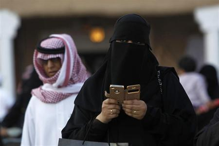 A woman using an iPhone visits the 27th Janadriya festival on the outskirts of Riyadh in this February 13, 2012 file photo. REUTERS/Fahad Shadeed/Files