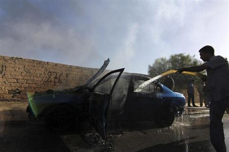 A man douses a smoking car with water, after it was bombed in the attempted assassination of Abdulsalam Al-Dus, a lieutenant colonel in the Libyan army, in Benghazi October 13, 2013. REUTERS/Stringer