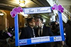 Brian Hirschberg (R) kisses his partner Gabriel Laureano holding up a frame while they attend marriage ceremonies of gay, lesbian and straight couples in Newark, New Jersey October 21, 2013. REUTERS/Eduardo Munoz