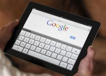 Una mujer con un iPad visitando la web de Google en Bordeaux, Francia, feb 4 2013. La fuerte demanda de tabletas como el iPad de Apple ayudará a que aumenten este año los envíos de dispositivos habilitados para internet, compensando la bajada de los de computadoras de escritorio y portátiles, dijo el lunes la compañía de análisis Gartner. REUTERS/Regis Duvignau