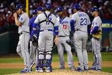 Oct 18, 2013; St. Louis, MO, USA; Los Angeles Dodgers starting pitcher Clayton Kershaw (left) walks back to the dugout after being relieved during the fifth inning in game six of the National League Championship Series baseball game at Busch Stadium. Scott Rovak-USA TODAY Sports