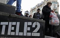 Люди проходят мимо офиса продаж Tele2 в Санкт-Петербурге 2 апреля 2013 года. Скандинавская телекоммуникационная группа Tele2 снизила долгосрочный прогноз финансовых результатов одновременно с публикацией данных о базовой прибыли в третьем квартале, которая оказалась ниже ожиданий рынка. REUTERS/Alexander Demianchuk