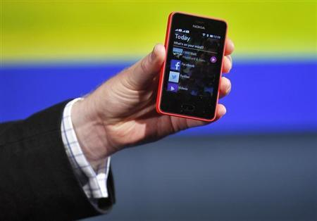 A Nokia official displays a new $99 phone in its mid-range Asha line at a launch in New Delhi May 9, 2013. REUTERS/Anindito Mukherjee