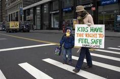 Женщина и ее сын участвуют в акции в поддержку ограничений на использование оружия в Нью-Йорке 21 января 2013 года. Двенадцатилетний американский школьник, вооруженный полуавтоматическим пистолетом, застрелил учителя математики и тяжело ранил двух одноклассников, после чего покончил с собой. REUTERS/Eduardo Munoz
