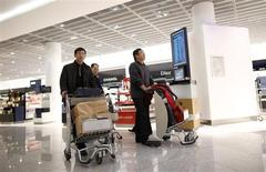 Men wheel shopping trolleys in a Duty Free store at the Fraport airport in Frankfurt November 14, 2012. REUTERS/Lisi Niesner