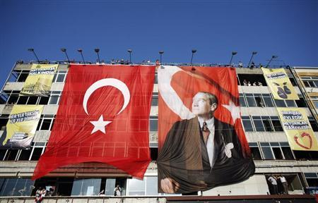 A building is decorated with a giant Turkish flag and a poster of modern Turkey's founder Mustafa Kemal Ataturk (R) during an anti-government protest at Kadikoy square in Istanbul July 7, 2013. REUTERS/Murad Sezer