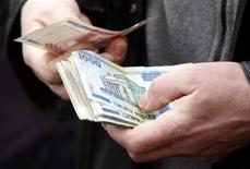 Мужчина пересчитывает купюры на рынке в Минске 31 марта 2013 года. Правительство Белоруссии вслед за Всемирным банком ухудшило прогноз на 2014 год и предложило Нацбанку смягчить денежно-кредитную политику ради стимулирования стагнирующей экономики. REUTERS/Vasily Fedosenko