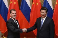 Российский премьер Дмитрий Медведев жмет руку председателю КНР Си Цзиньпину перед встречей в Пекине 22 октября 2013 года. Российские нефтегазовые компании подписали во вторник сразу несколько соглашений с китайскими потребителями углеводородов, которые обещают превратить Китай в крупнейшего потребителя нефти и газа из РФ. REUTERS/Kota Endo/Pool