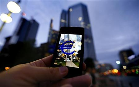 A passerby uses his smartphone to take a picture of the euro sign landmark in front of the headquarters of the European Central Bank (ECB) in Frankfurt September 2, 2013. REUTERS/Kai Pfaffenbach