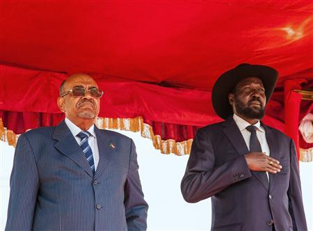 Sudan's President Omar al-Bashir (L) and his host South Sudan's President Salva Kiir stand for their national anthems at Juba Airport October 22, 2013. REUTERS/Adriane Ohanesian