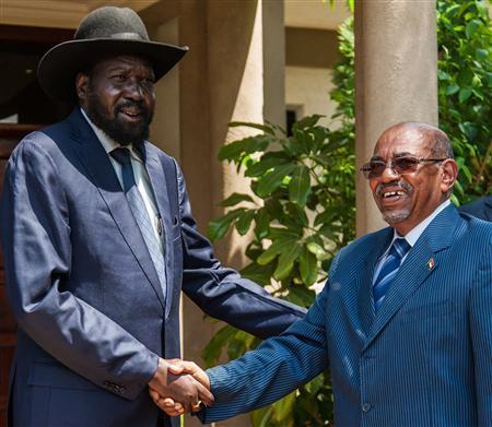 Sudan's President Omar al-Bashir (R) shakes hands with his host, South Sudan's President Salva Kiir, at Juba Airport October 22, 2013. REUTERS/Adriane Ohanesian