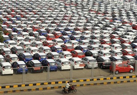 A man rides his motorbike past parked Hyundai cars ready for shipment at a port in the southern Indian city of Chennai October 1, 2013. REUTERS/Babu
