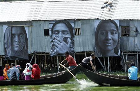 Boats carrying slum dwellers pass photographs of garment workers taken by students of the Counter Foto photography department, by the waterfront of Korail slum at Gulshan area in Dhaka September 13, 2013. REUTERS/Andrew Biraj/Files