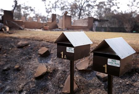 The remains of a home that was destroyed by a bushfire can be seen behind two letter boxes in the Blue Mountains suburb of Winmalee, located around 70 km west of Sydney, October 21, 2013. REUTERS/David Gray
