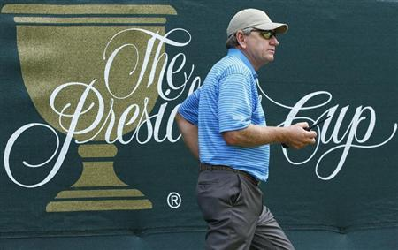 International Team captain Nick Price of Zimbabwe carries a two-way radio during the second practice round for the 2013 Presidents Cup golf tournament at Muirfield Village Golf Club in Dublin, Ohio October 2, 2013. REUTERS/Jeff Haynes