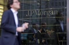 Люди отражаются в окнах офиса JP Morgan в Лондоне 19 сентября 2013 года. Предварительное соглашение на сумму $13 миллиардов, заключенное JPMorgan Chase & Co с американским правительством, может в результате стоить банку около $9 миллиардов после налогов, так как большая часть соглашения, вероятно, подлежит вычету при исчислении налоговой базы, сообщили два источника, знакомые с ситуацией. REUTERS/Neil Hall