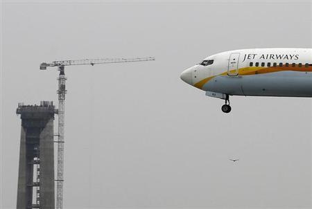 A Jet Airways passenger plane prepares to land past a new air traffic control tower under construction at the Indira Gandhi International Airport in New Delhi July 29, 2013. REUTERS/Adnan Abidi/Files
