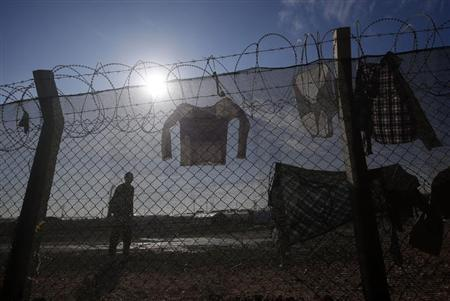 A man stands behind a fence on which clothes are hung at the refugee camp near the Turkish border town of Ceylanpinar, Sanliurfa province December 1, 2012. REUTERS/Laszlo Balogh