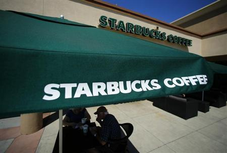 Customers enjoy their drinks outside a newly designed Starbucks coffee shop in Fountain Valley, California August 22, 2013. REUTERS/Mike Blake