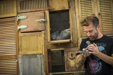 Artista Duke Riley examina seu pombo Johnny Dinamite enquanto se prepara para exibição na Galeria Magnan Metz, em Nova York, 21 de outubro de 2013. Graças ao artista Duke Riley, o aparato norte-americano de vigilância aérea enfrenta novos inimigos voadores: pombos-correios. Riley treinou pombos para contrabandear charutos de Havana para Key West, na Flórida, enquanto outras aves filmaram a viagem de 160 quilômetros com câmeras especiais. 21/10/2013 REUTERS/Brendan McDermid