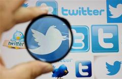 Una persona sostiene una lupa sobre una pantalla de computadora con diversos logos de Twitter en Skopje, sep 10 2013. La red social de microblogs Twitter Inc obtuvo una línea de crédito por 1.000 millones de dólares, una medida esperada antes de lanzar una oferta pública de acciones (OPI), según reveló el martes la compañía en documentos legales. REUTERS/Ognen Teofilovski