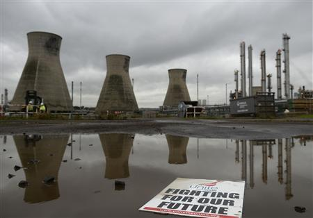 A placard floats in a puddle in a car park in front of the Grangemouth refinery in Scotland October 21, 2013. REUTERS/Russell Cheyne