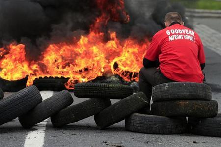 Flames and smoke rise from burning tyres as a worker sits on a barricade blocking the entrance of U.S. tyre-maker Goodyear's plant to protest job cuts in Amiens, northern France, June 3, 2013. REUTERS/Benoit Tessier