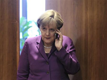 Germany's Chancellor Angela Merkel uses her mobile phone before a meeting at a European Union summit in Brussels December 9, 2011. REUTERS/Yves Herman