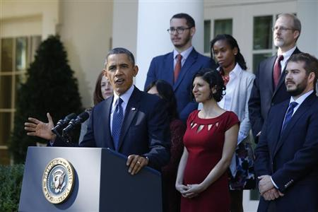 U.S. President Barack Obama stands with Affordable Care act registrants and beneficiaries as he speaks about healthcare from the Rose Garden of the White House in Washington October 21, 2013. REUTERS/Jason Reed