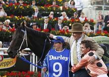 Jockey Luke Nolen (R) embraces Black Caviar trainer Peter Moody after winning the TJ Smith Stakes at Royal Randwick racecourse in Sydney April 13, 2013. REUTERS/Daniel Munoz