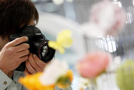 A man tries out a Canon Inc's new digital SLR camera EOS-1D X at a Canon showroom in Tokyo April 24, 2012. REUTERS/Toru Hanai