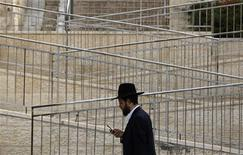An ultra-Orthodox Jew holds a mobile phone as he walks in Ramat Shlomo, a religious Jewish settlement in an area of the occupied West Bank Israel annexed to Jerusalem, in this May 10, 2010 file photo. REUTERS/Baz Ratner/Files